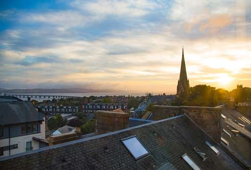 A sunset view over Dundee rooftops toward the Tay Bridge
