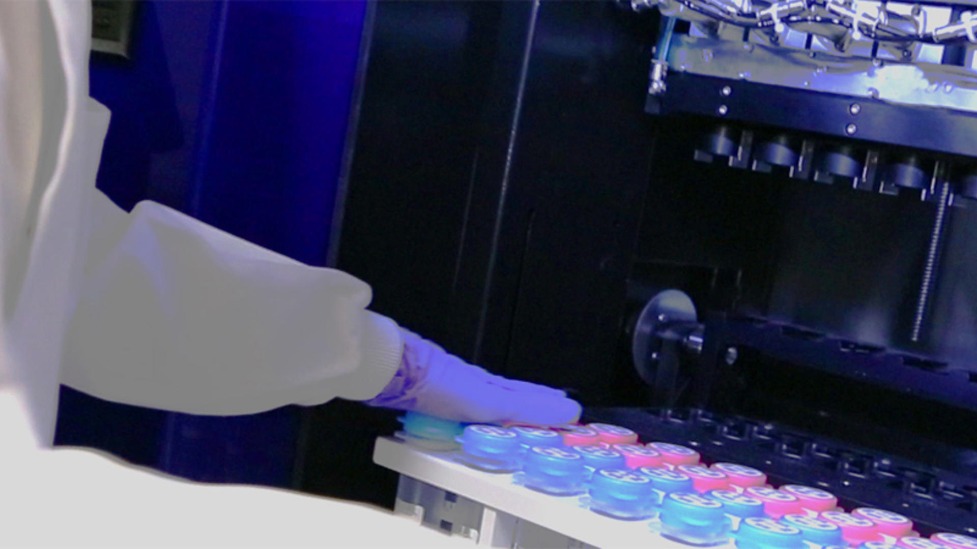 A person in PPE moving samples into or out of a fridge