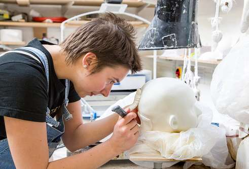a student working in a ceramic head
