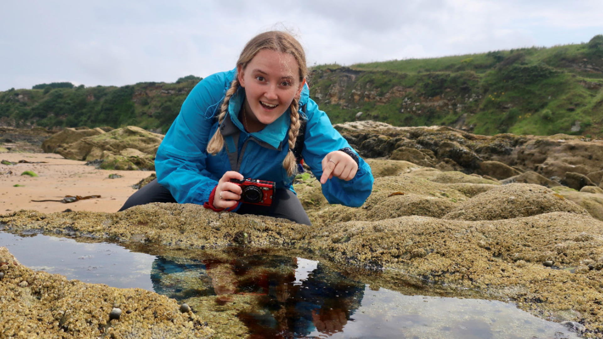 Elizabeth Mills crouching on rocks, pointing camera into a rockpool