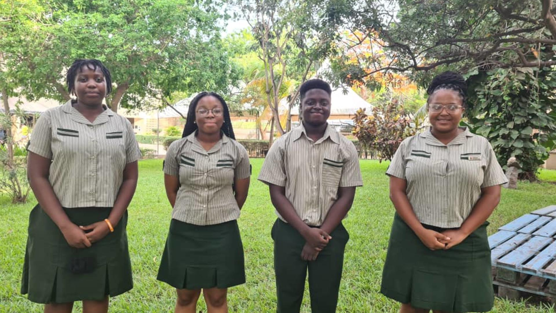 Team members from TIS standing in brown uniform smiling with trees and grass in background