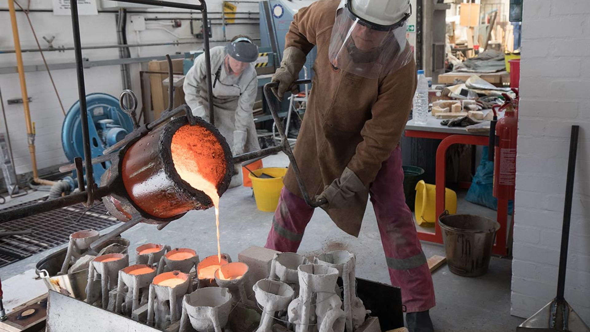 a person in protective gear pouring molten metal into moulds