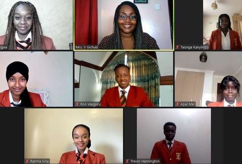 Brookhouse school pupils in red uniform smiling on video call