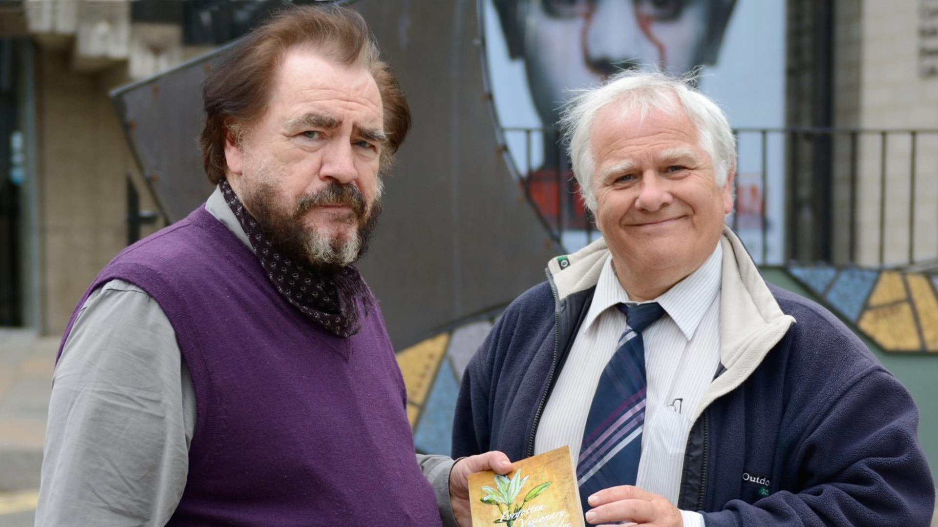 Eddie Small presenting Brian Cox with a copy of his book of Mary Lily Walker