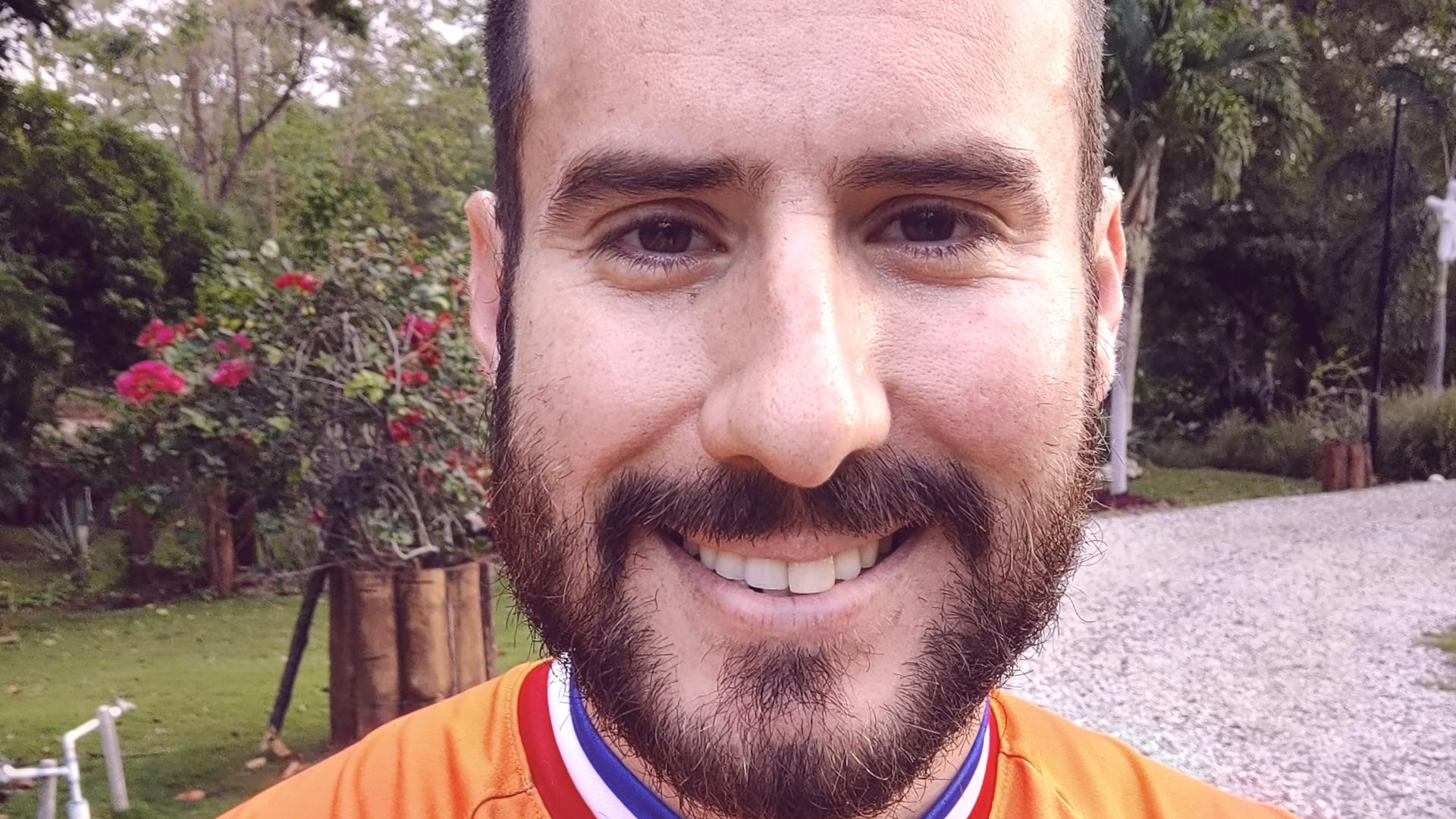 Alejandro smiling at camera wearing orange jumper