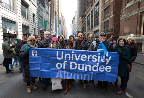 A group of people holding a University of Dundee banner