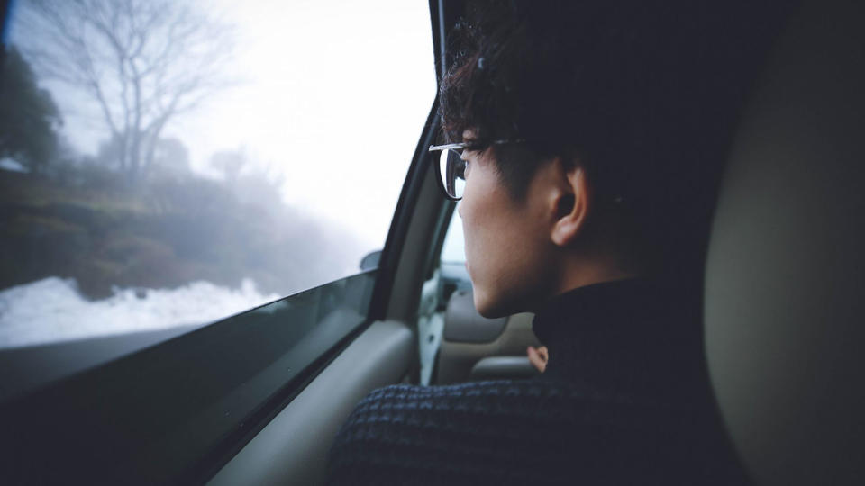 Boy looking out of car window at grey landscape