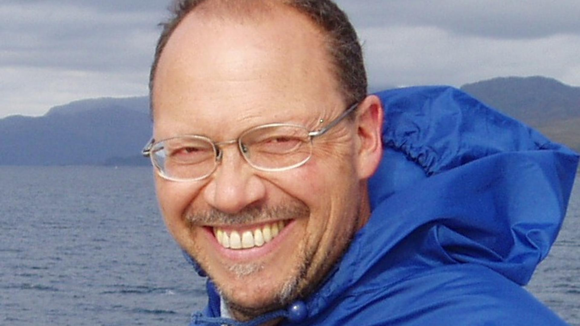 Professor Emanuele Trucco smiling. Wearing a blue jacket with the sea behind him