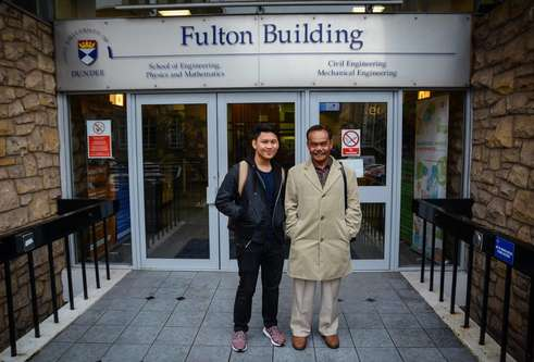 Hakim and Dato standing in front of the Fulton Building's main doors