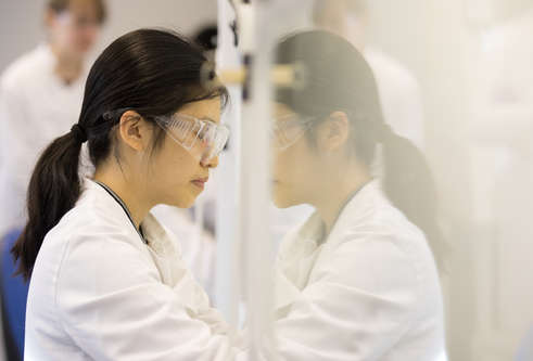 a woman working in a lab wearing safety goggles