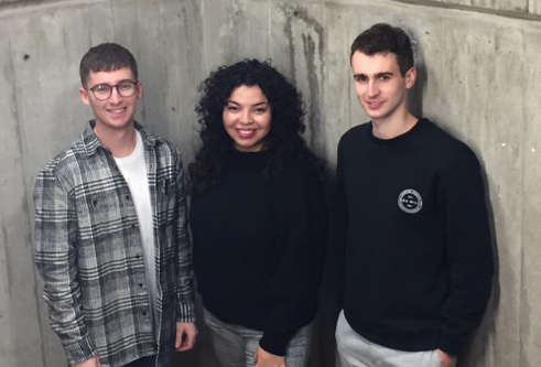 Three students standing before a concrete wall
