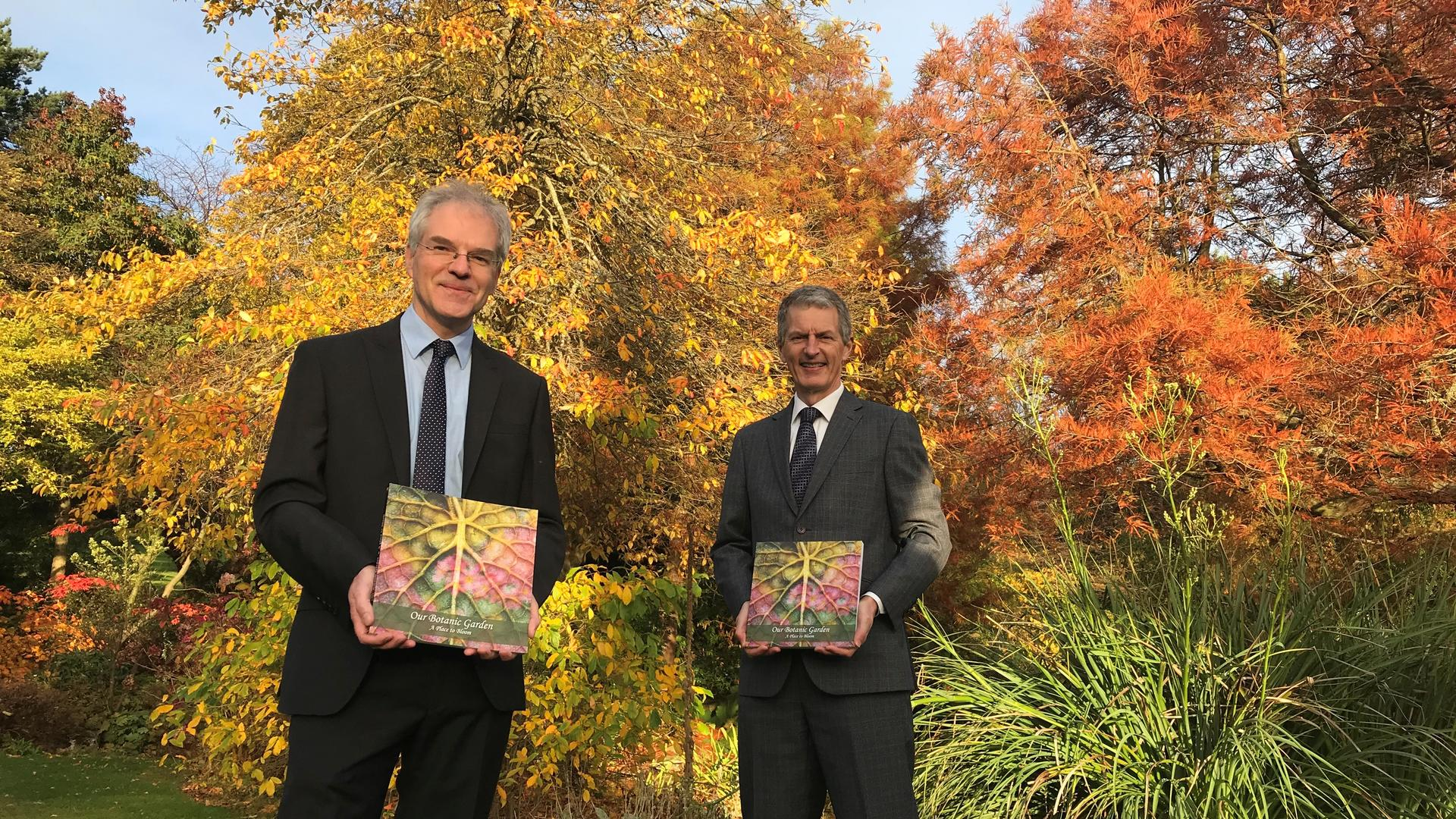 Dr Mark McGilchrist, Chair, Friends of the University Botanic Garden, and Principal Professor David Maguire holding the anthology