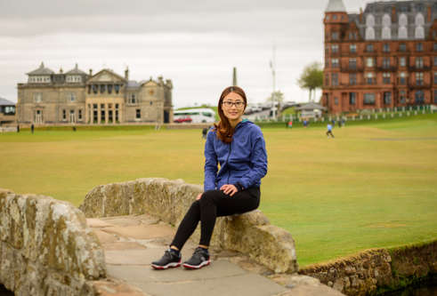 Yan Jiang sitting on the Swilken Bridge in St Andrews, on the Old Course