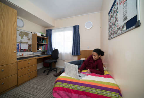 Student lying on bed in student accommodation