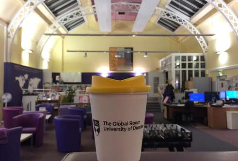 A photograph of a Global Room branded mug with the Global Room behind