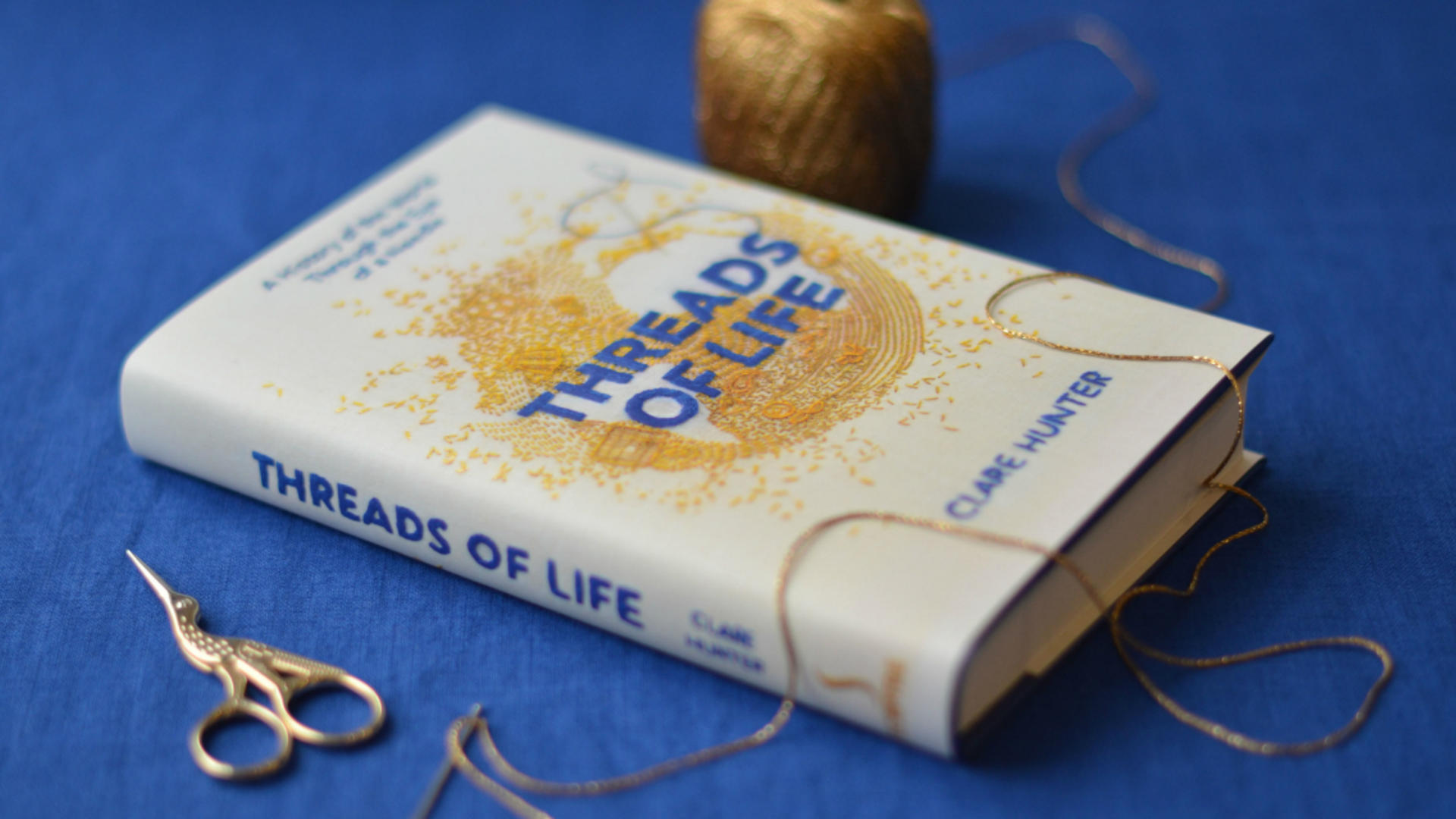 Threads of life hardback book surrounded by thread and scissors