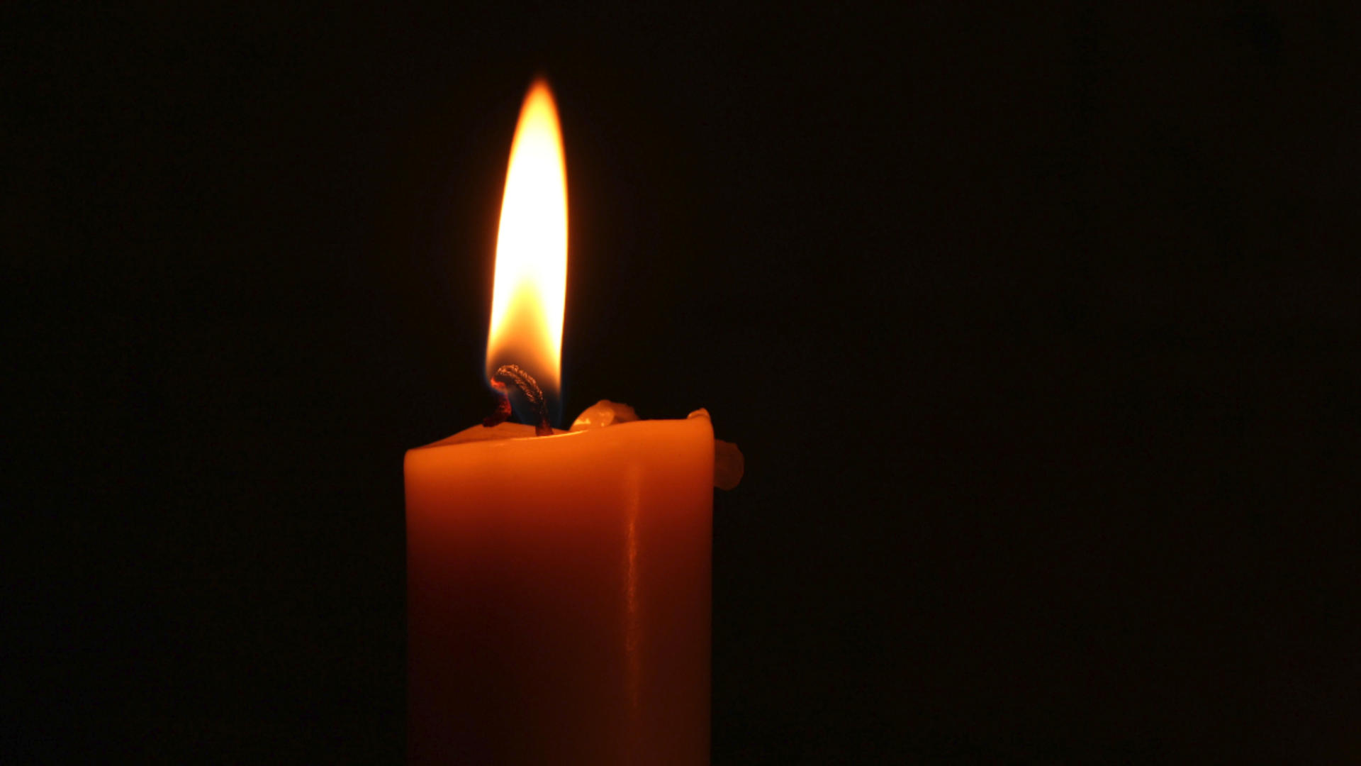 Red candle in front of black background