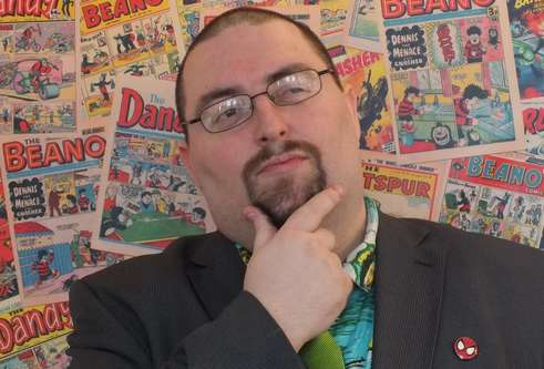 Chris Murray in front of a wall of comics
