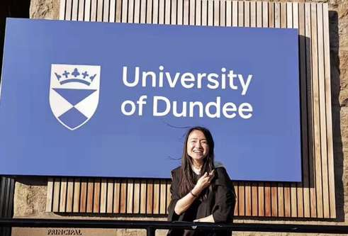 Jing Chen standing in front of the University of Dundee sign