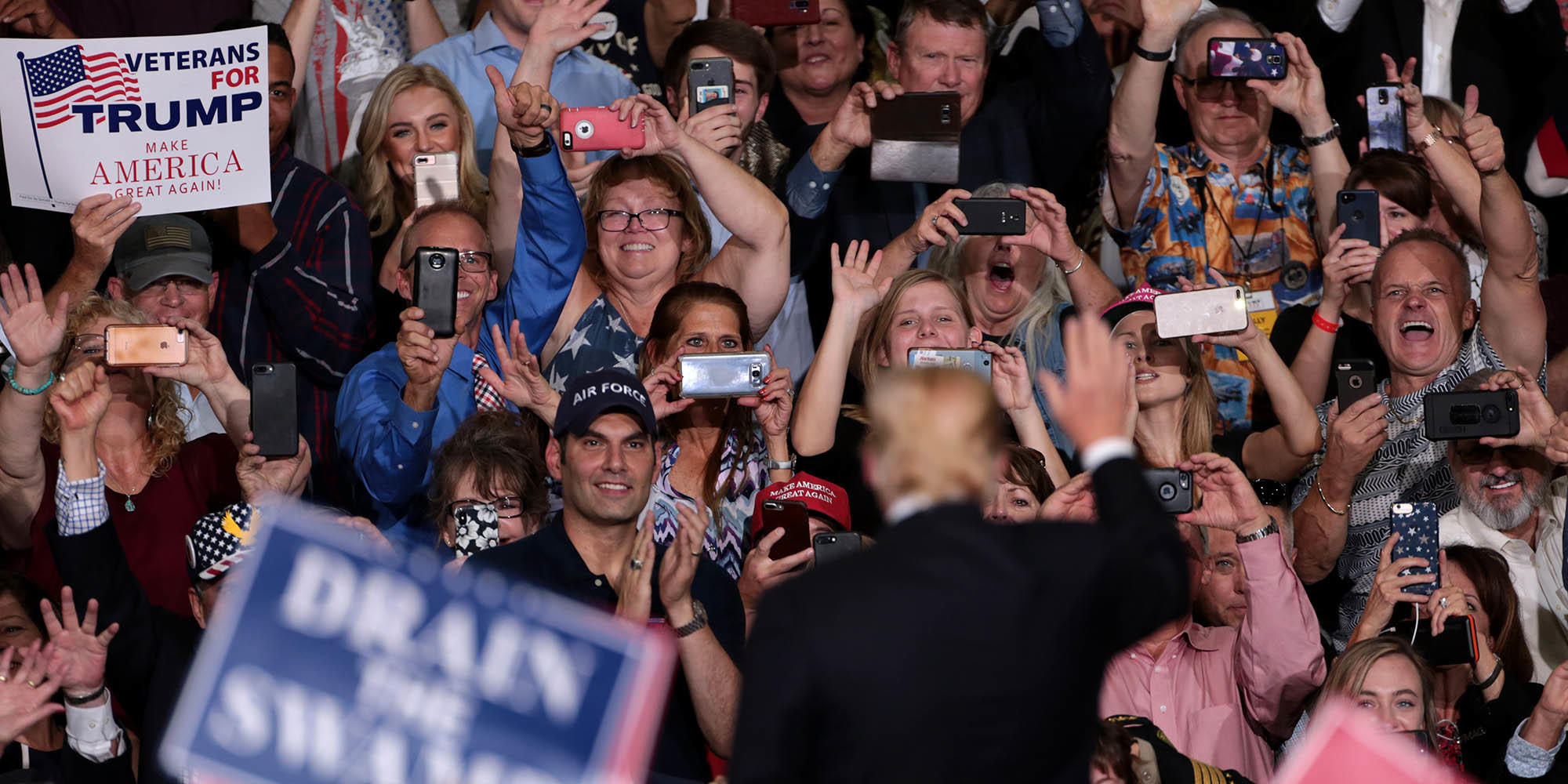 Donald Trump out of focus from behind waving to an in-focus crowd