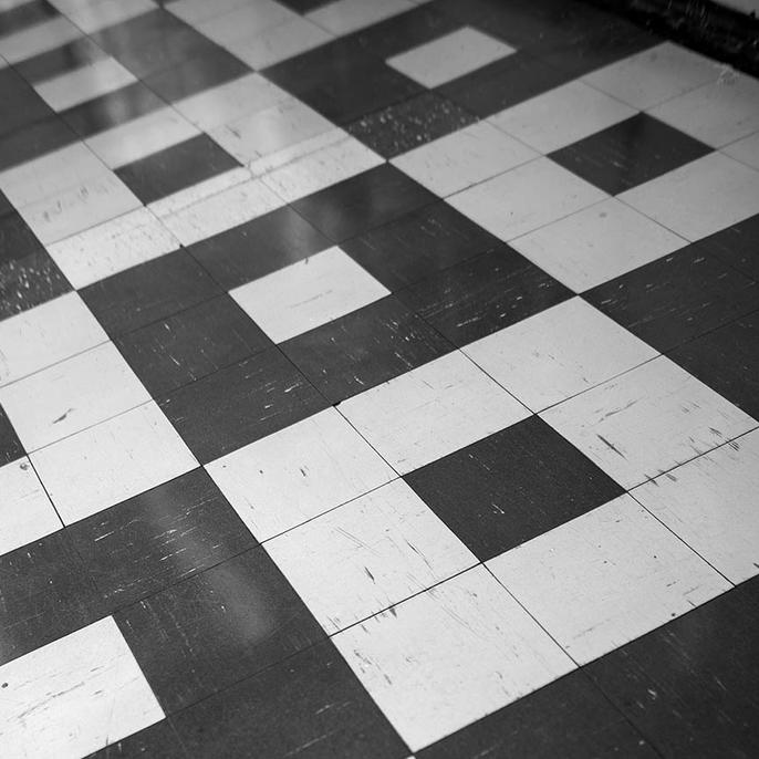 A photo of tiled flooring with a black and white square pattern