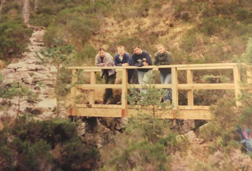 Four men in their twenties lean against the handrail on a freshly built, unpainted, wooden bridge. The bridge crosses a small rocky gorge surrounded by foliage and further rock formations.